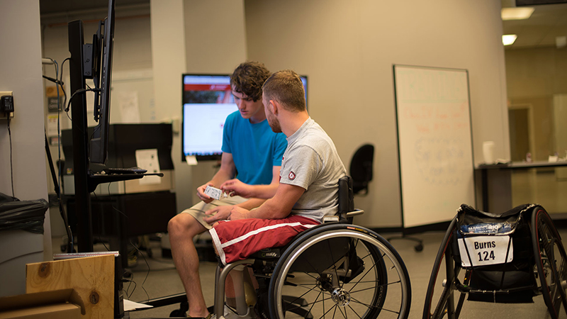 Two students sitting in a lab, one in a wheelchair
