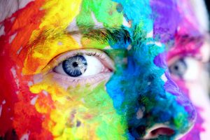 person's face covered in multicolored paints