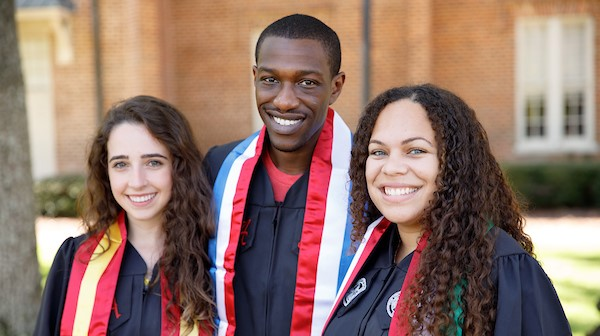 three students in graduation attire