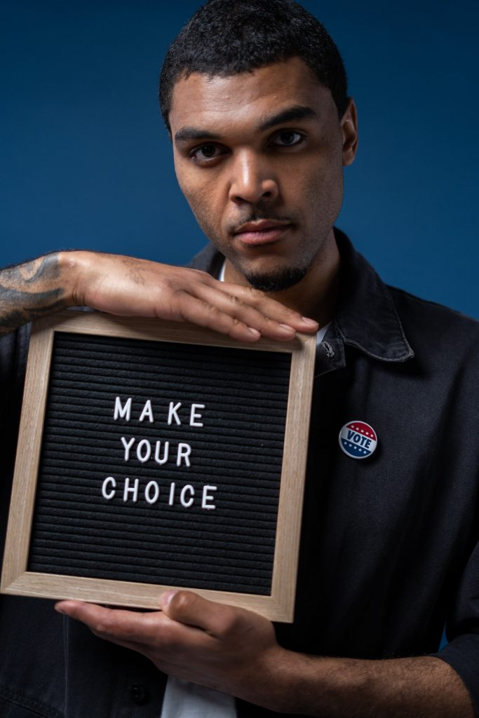 Man holding sign that says make your choice