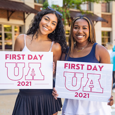 Students holding First Day UA signs from fall 2021